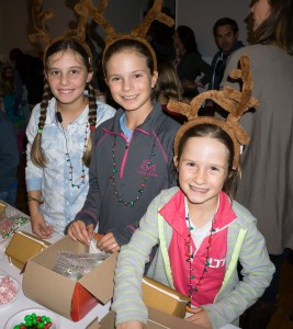 Three reindeer get ready to build gingerbread houses.