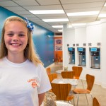 Adeline, one of the high school students Sonya and Bob employ at their new Frozen Yogurt shop, shows off the new store.
