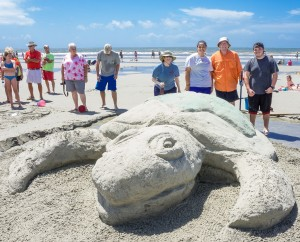 Sand sculptors and onlookers admire Spoleto-worthy works.