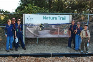 Andrew Killough, left of the sign holding paper, at the dedication ceremony for the SIES Nature Trail in 2008. Today Killough's Eagle Scout project is installing new signs on the newly revitalized trail.