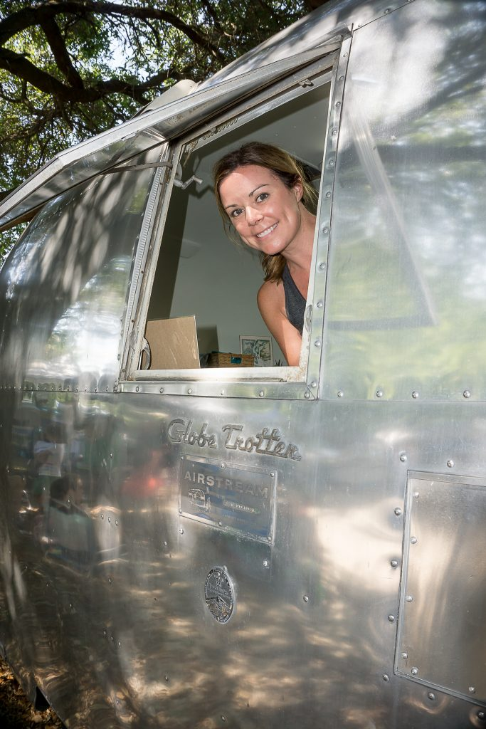 Emily Richardson of Emerson Row peeks out the window of her Airstream.