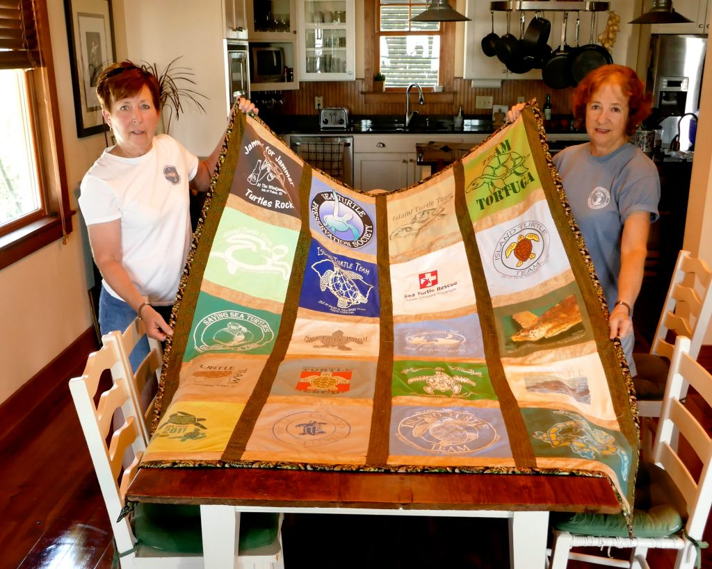 Barb Gobien and Mary Pringle with the Turtle Quilt to be raffled at the party.